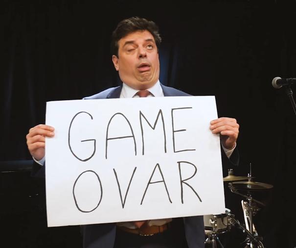 """Aktér, držícího v ruce ceduli """"Game Ovar"""" a parodující prezidentovu mimiku."""