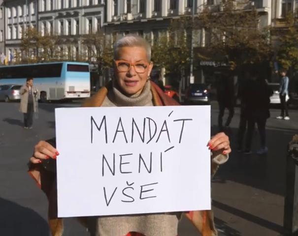 """Operní pěvkyně Dagmar Pecková drží transparent s nápisem """"Mandát není vše""""."""