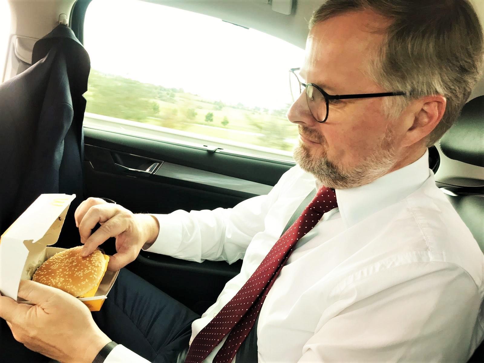 Petr Fiala jící burger